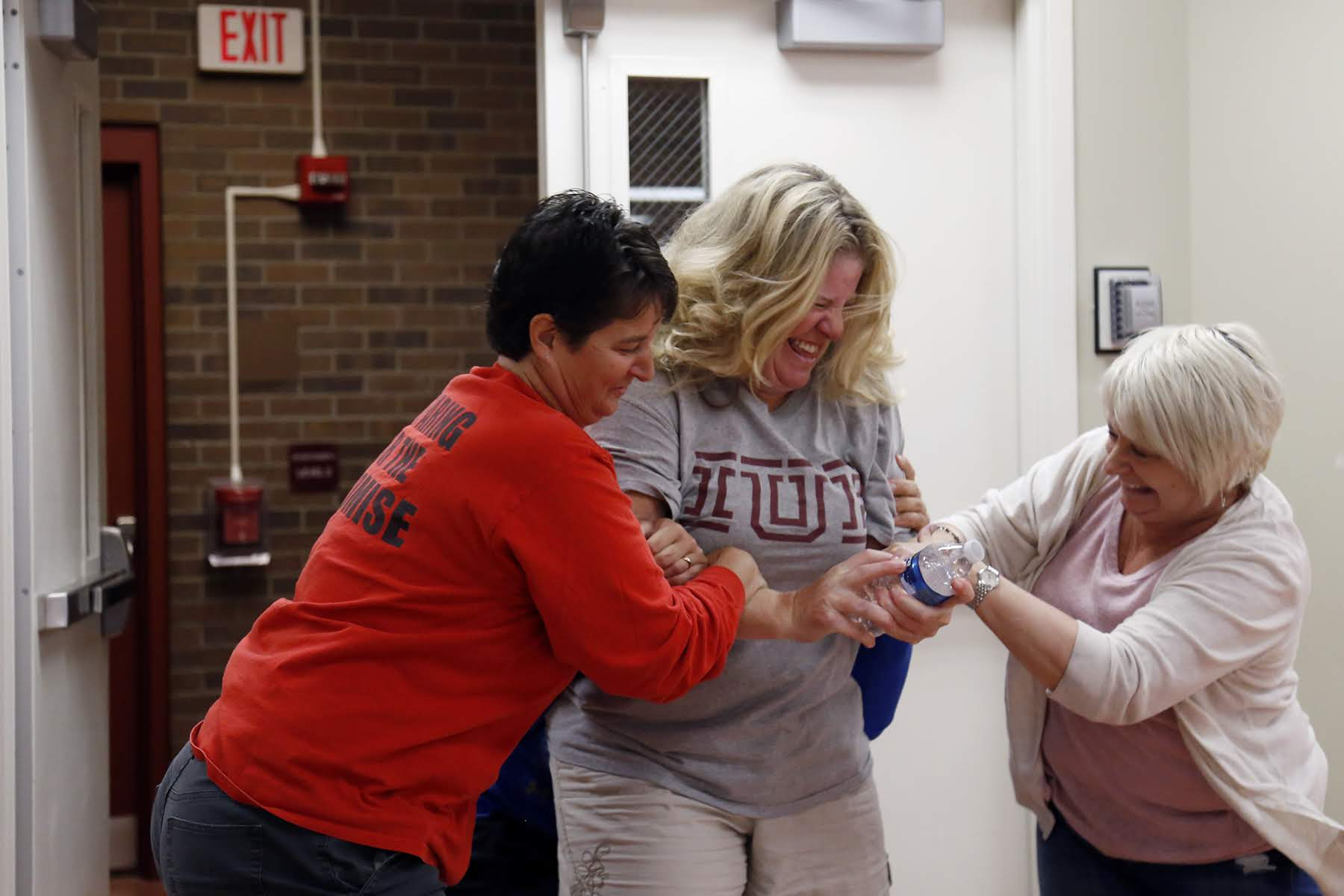 Using a water bottle as a stand-in for a gun, Karen Arnold (center), principal at Fulton PreK-5, is swarmed by Patti Camper (left), principal at Arsenal 6-8, and LouAnn Zwieryznski (right), principal at Liberty K-5, during ALICE training on Aug. 7. (Photo by Ryan Loew/PublicSource)