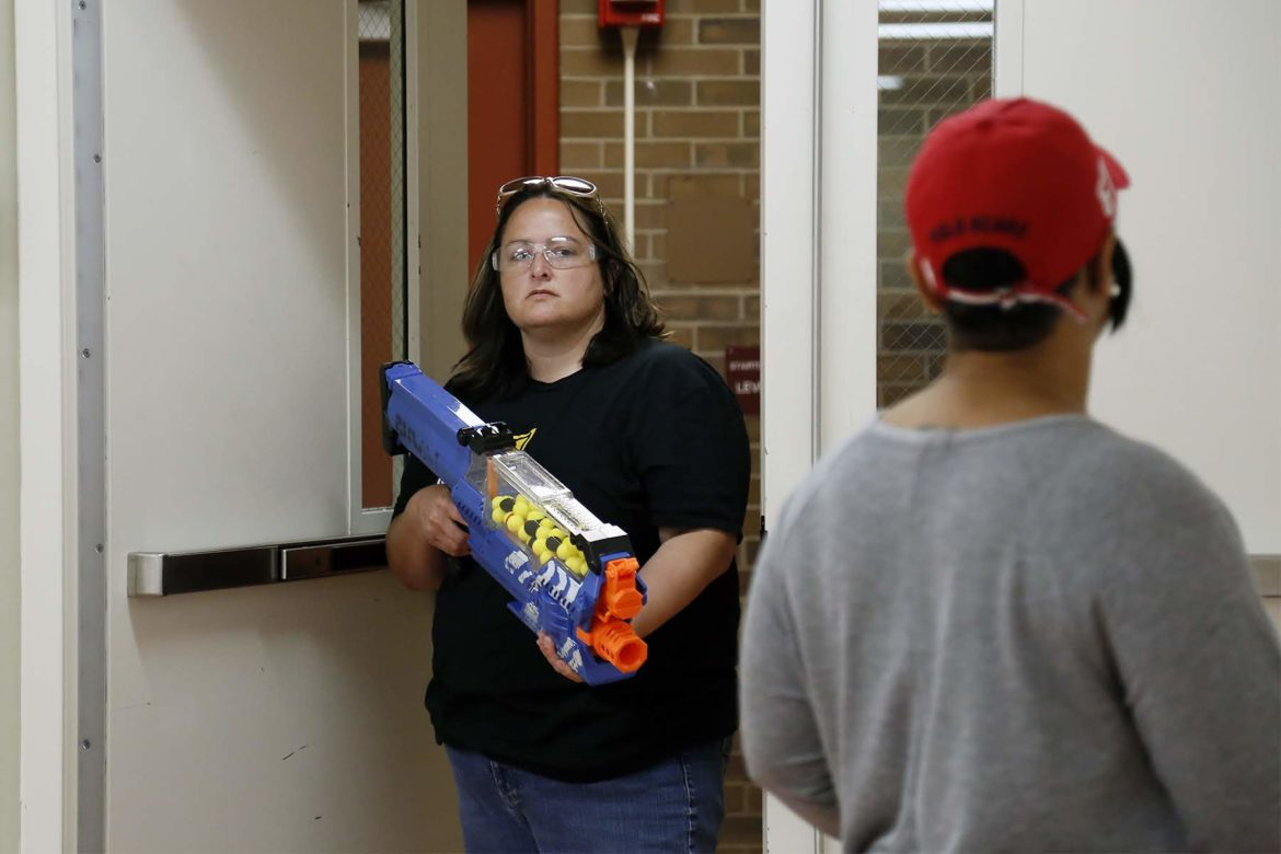 Arlington PreK-8 assistant principal Beth Delawder holds a Nerf gun during ALICE training on Aug. 7. (Photo by Ryan Loew/PublicSource)