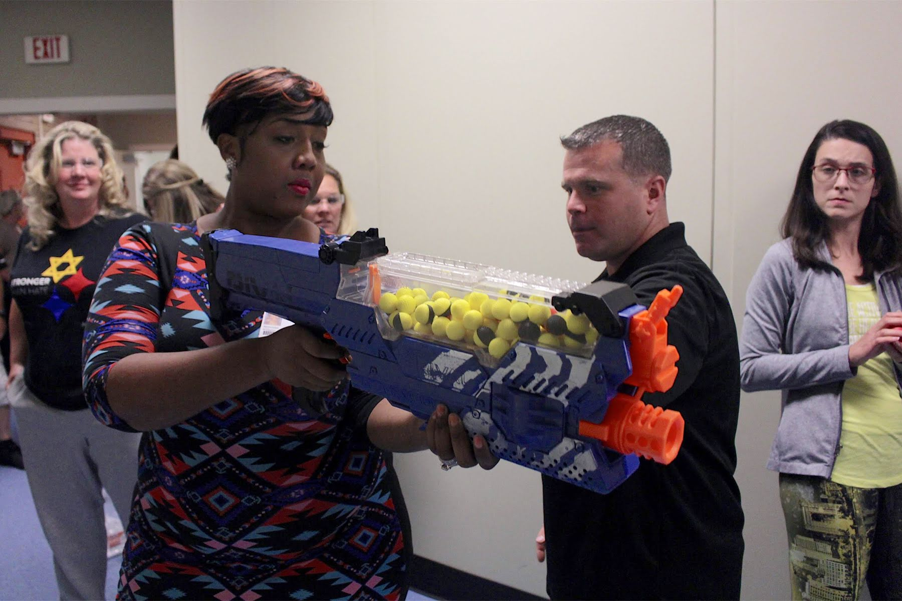 ALICE Trainer, John Lubawski instructs Merecedes Williams, a PPS employee how to use Nerf gun prior to an active shooter drill. (Photo by Jay Manning/PublicSource)