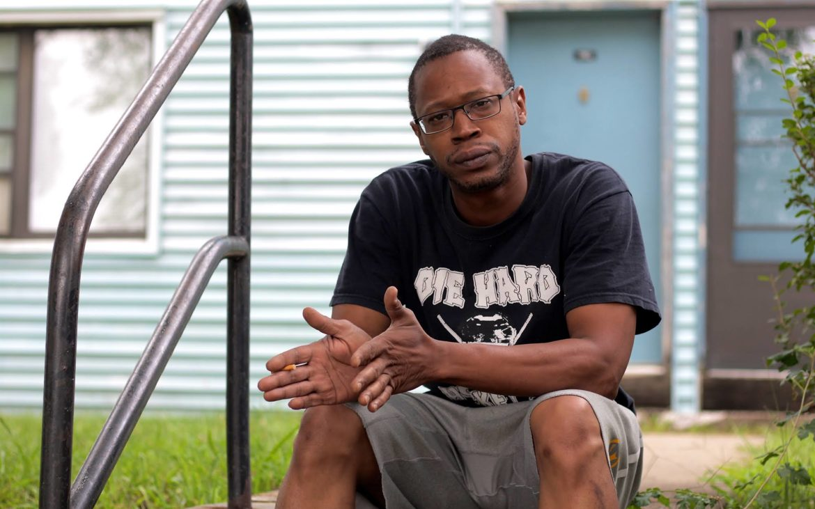 Devin McClain sitting outside of friend Geraldine Shields' new apartment after both had been displaced by the De Ruad Street fire. (Photo by Jay Manning/PublicSource)