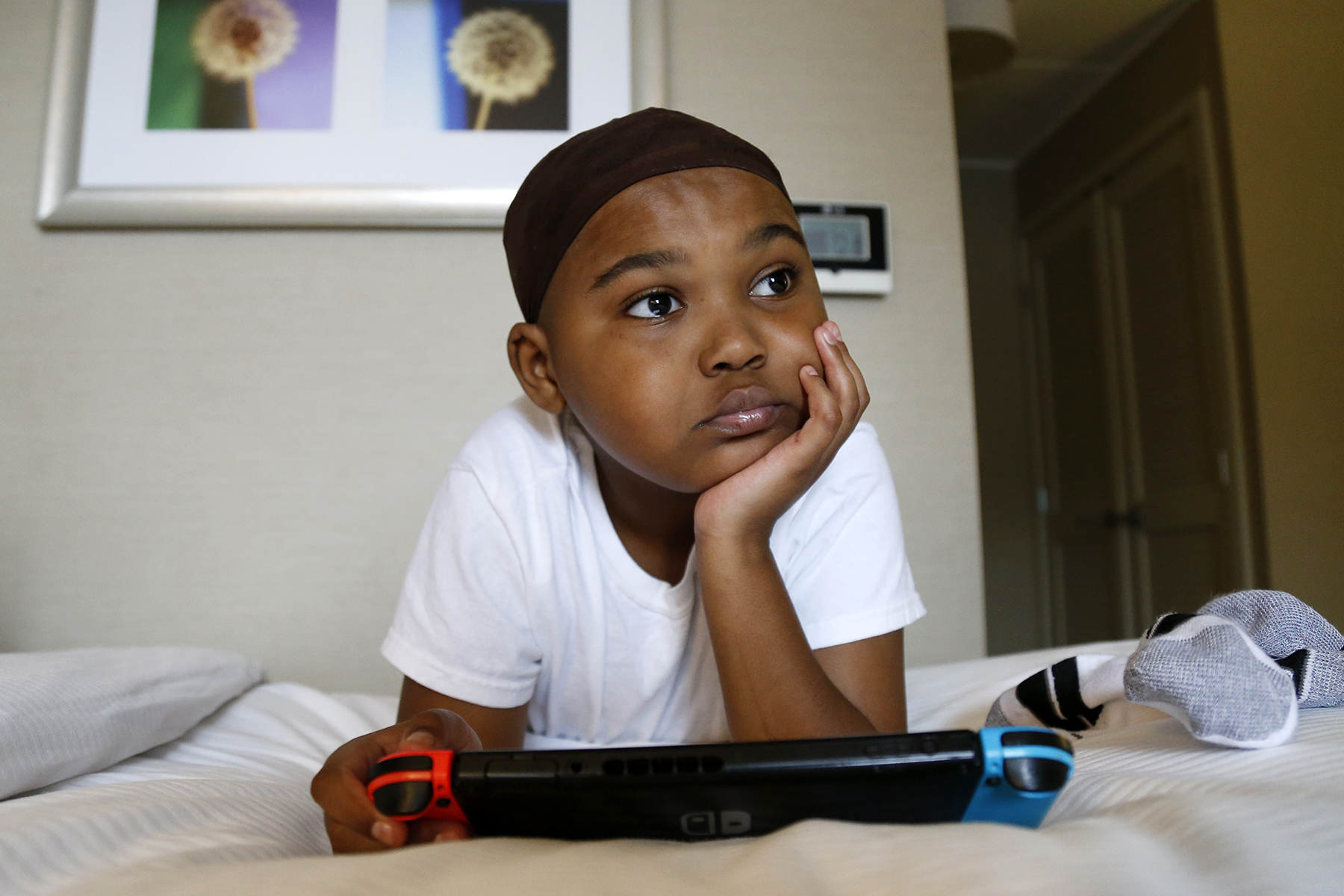 Desirea Pate's 9-year-old son Ny'Air plays Super Smash Bros Ultimate on his Nintendo Switch while they stay at a hotel in Green Tree. Desirea is uncertain where she and her son will have to call home next. (Photo by Ryan Loew/PublicSource)