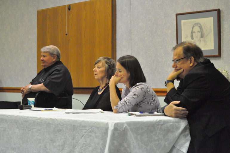 Rev. Jack Bendik, Lois Campbell, Mary Swindal and Frank Almade spoke on a Monday panel on parish consolidation. They are sitting at a table looking resigned.