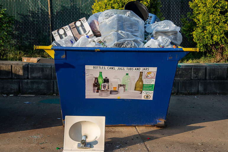A recycling container in Construction Junction's drop-off lot in North Point Breeze. The poster shows the bottles, cans, tubs, jugs and jars that can be recycled in the City of Pittsburgh. (Photo by Teake Zuidema/PublicSource)
