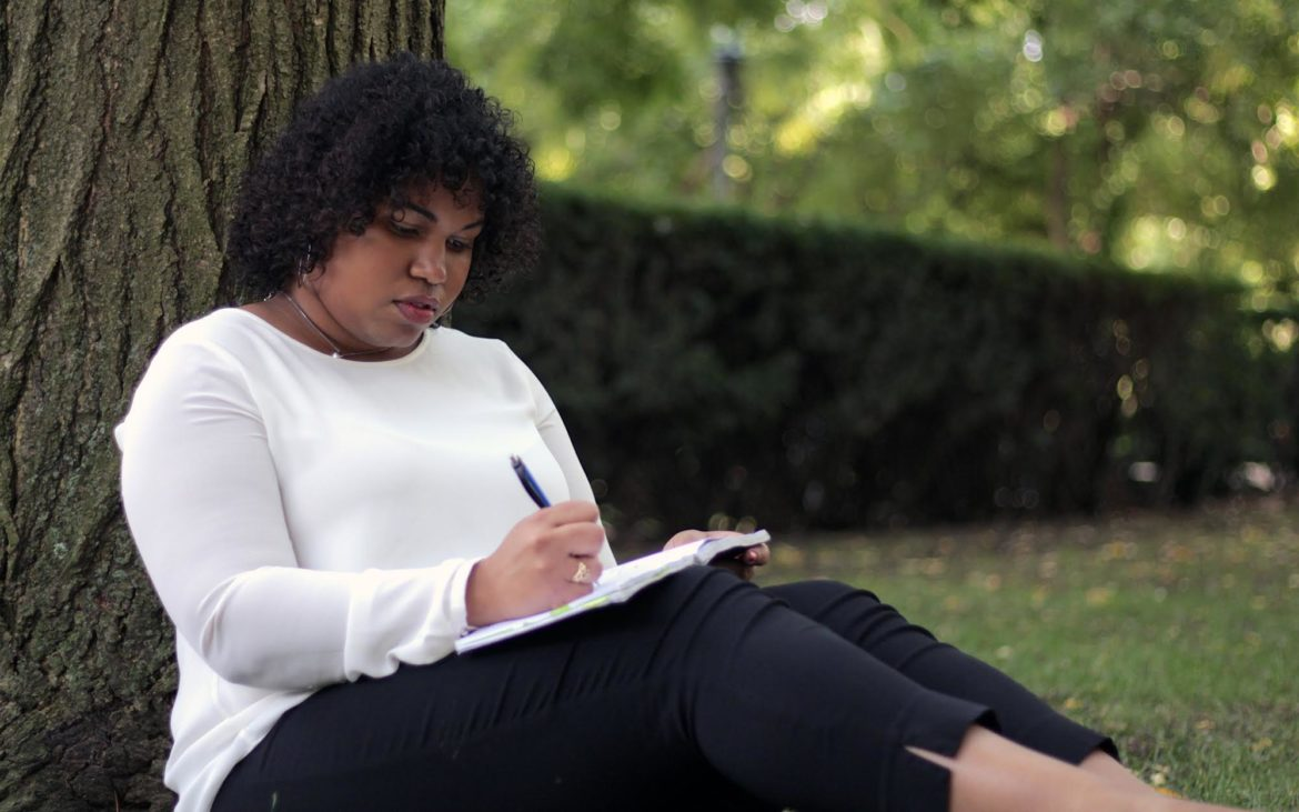 Patrice Alaquiva takes notes under a tree outside of the Cathedral of Learning (Photo by Jay Manning/PublicSource)