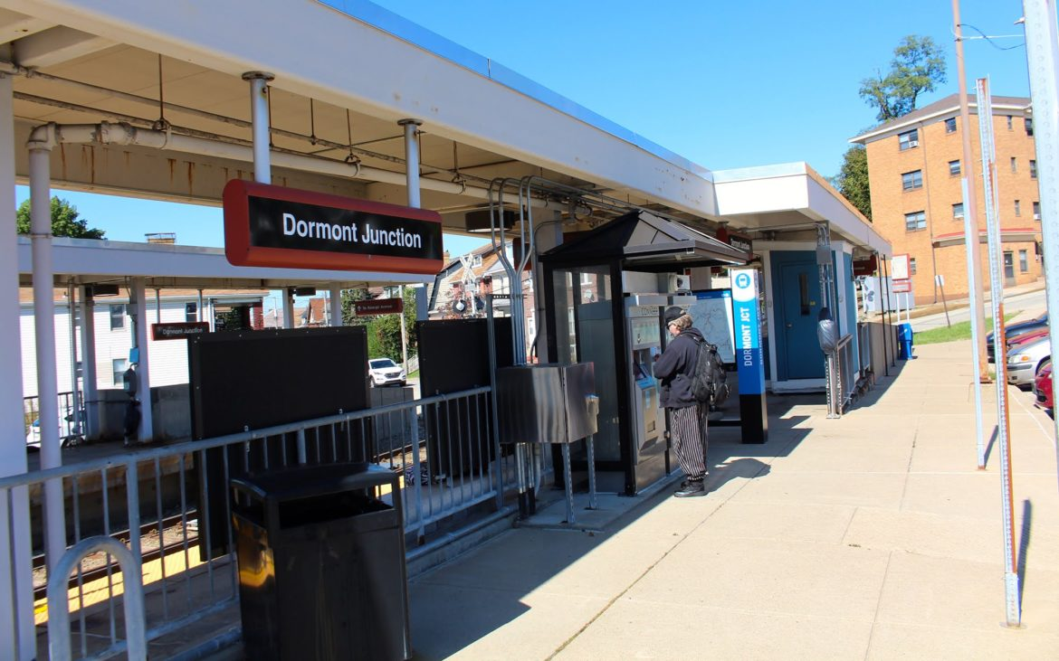 A passenger stands at a ConnectCard kiosk at Dormont Junction transit station.
