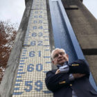 Local newsman Jim Casto stands up against the tiled river height gauge along the entrance of the floodwall in Huntington, West Virginia. (Liam Niemeyer, Ohio Valley ReSource)
