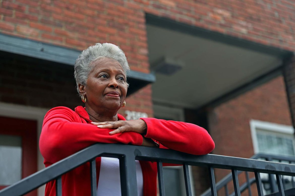 Woman in red shirt standing on balcony of the Oakland Affordable Living complex