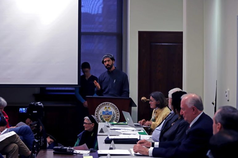 man at podium speaking to board members