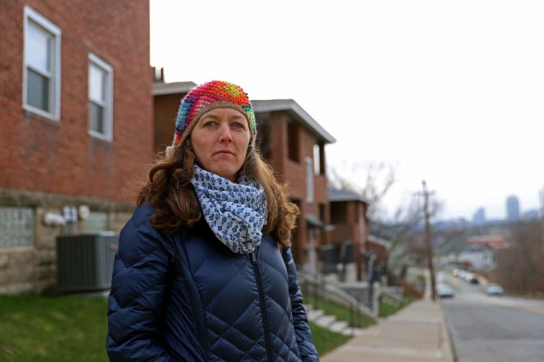 A woman in a winter scarf and hat standing outside of an affordable housing complex project she manages.