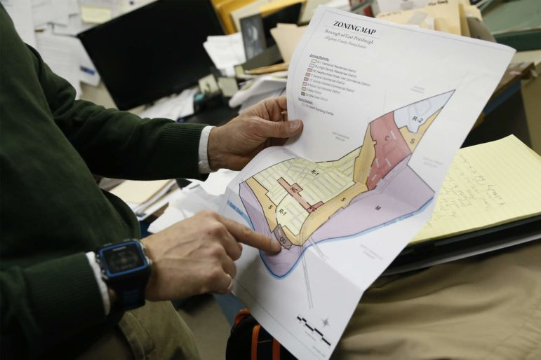 East Pittsburgh Borough Manager Seth Abrams points out a section of a zoning map of the borough. (Photo by Ryan Loew/PublicSource)