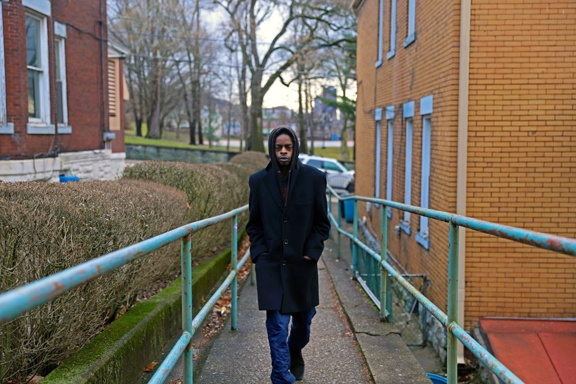 Man in a long black coat with his hood up and hands in his pockets walks along a sidewalk toward the camera.