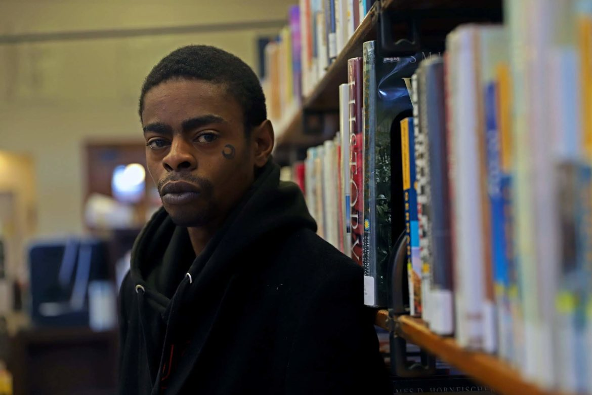 Jeffrey Bolden stands looking at the camera with his back facing a shelf of books at the Lawrenceville Branch of the Carnegie Library of Pittsburgh.