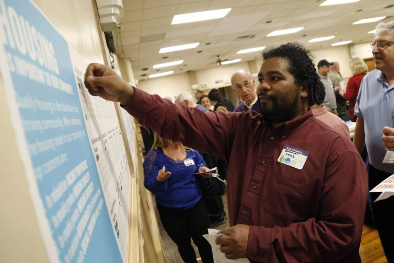 Along with other participants at a community planning event, Jonathan Reyes, East Pittsburgh councilman and arts and culture facilitator at the Braddock Carnegie Library, places stickers on a large sheet prioritizing actions and and others would like to see occur in the boroughs of Braddock, East Pittsburgh and North Braddock. (Photo by Ryan Loew/PublicSource)