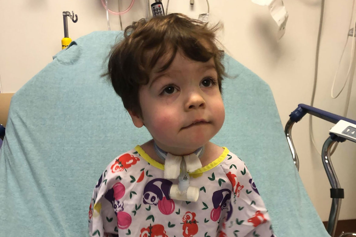 A brown haired toddler with a tracheotomy wears a hospital gown covered in panda bears as he sits on a hospital bed.
