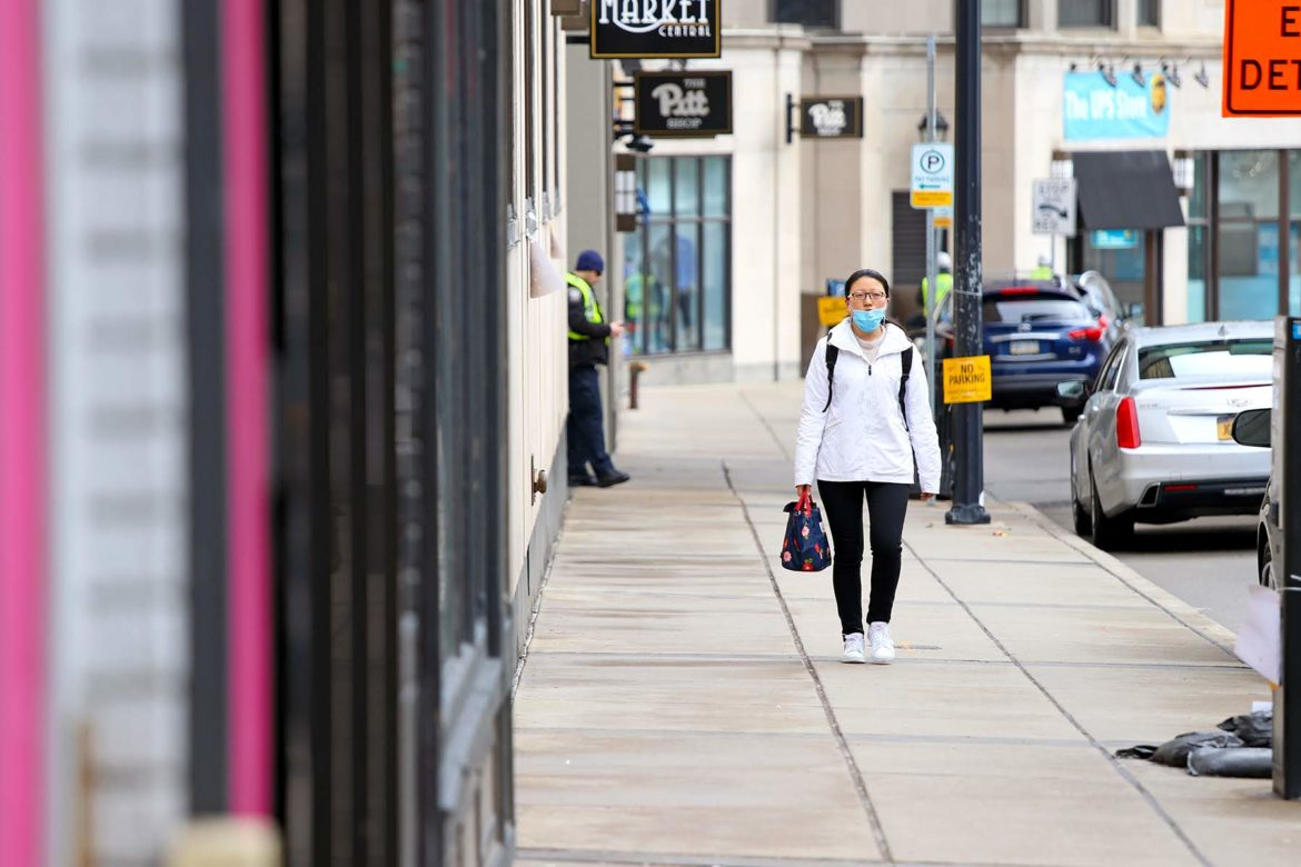 A woman walks along Forbes Avenue on University of Pittsburgh's campus on March 19. (Photo by Jay Manning/PublicSource)