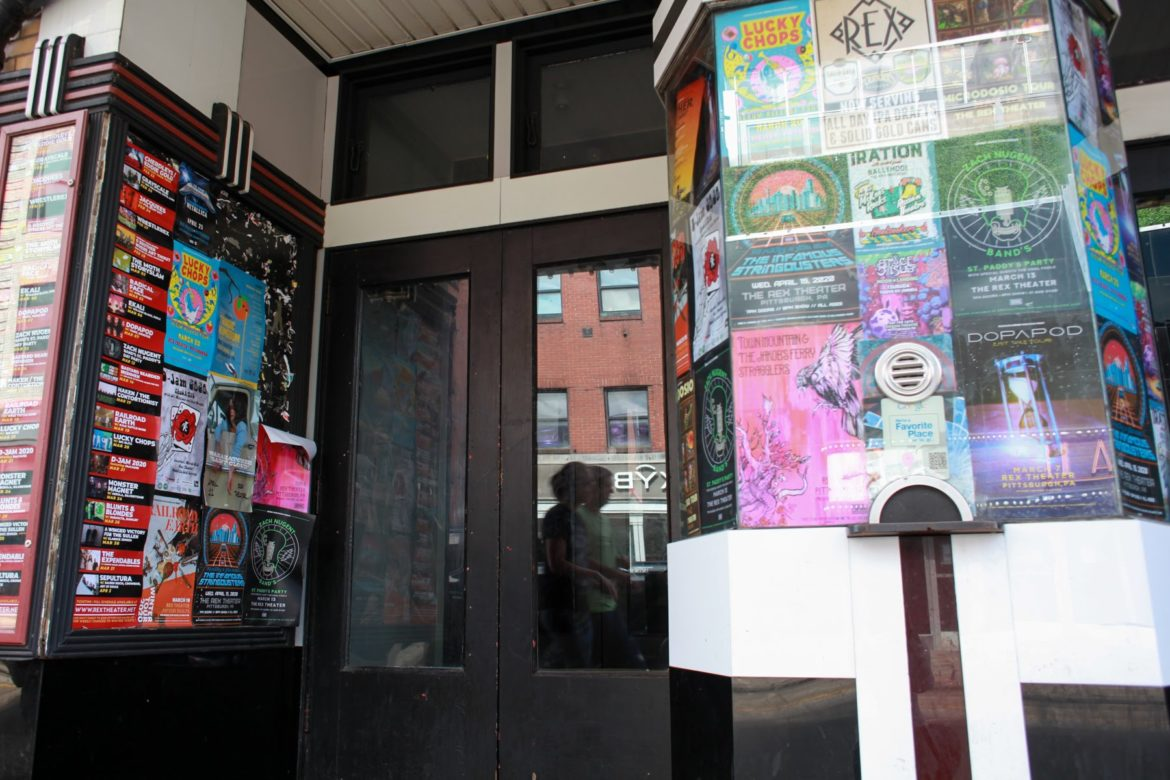 The windows of the Rex Theater in the South Side promote posters of the March and April shows that have been either canceled or postponed due to the coronavirus. (Photo by Kimberly Rowen/PublicSource)