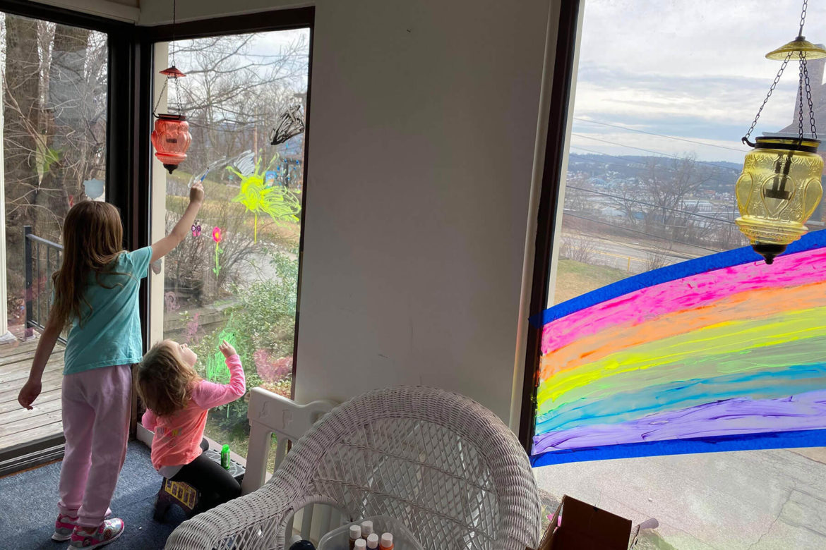"Annalise, 7, and Carys Mehlo, 3, of Bellevue paint rainbows on their windows overlooking the Ohio River Valley. Mother Alisa notes that it is not window paint, but they can scrape it off later. ""It's complete anarchy around here."""
