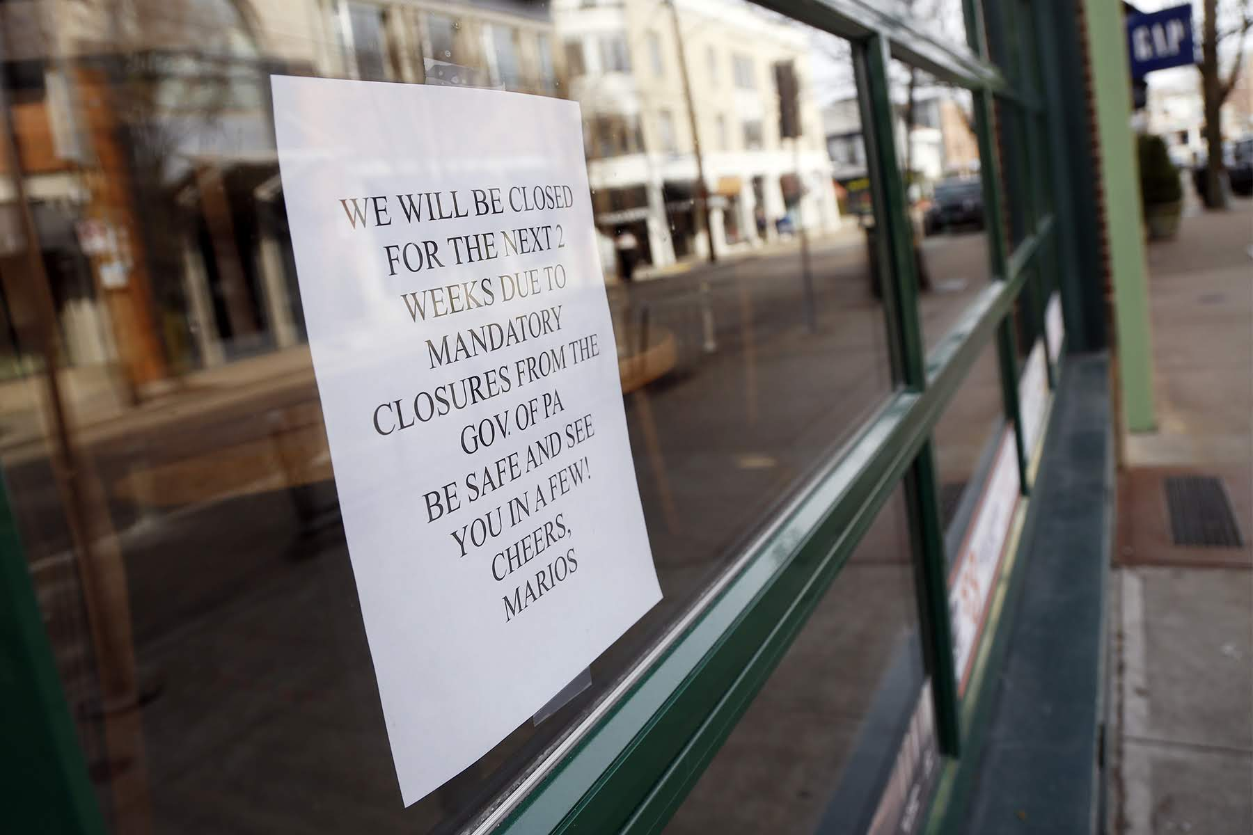 A sign posted in a window at Mario's East Side Saloon in Shadyside lets customers know they are temporarily closed. (Photo by Ryan Loew/PublicSource)