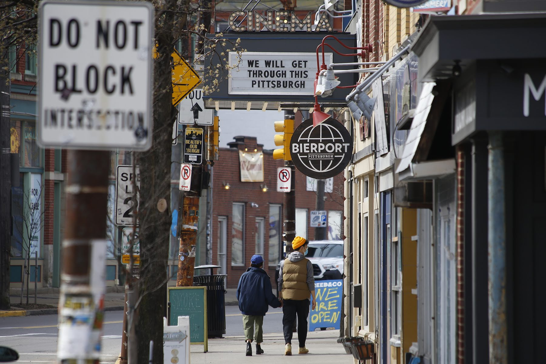 "People walk along Butler Street in Lawrenceville near Row House Cinema on March 18, where a marquee sign reads, ""We will get through this Pittsburgh."" (Photo by Ryan Loew/PublicSource)"
