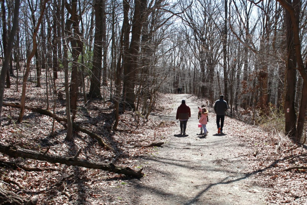 People take advantage of a sunny afternoon along a trail in North Park on March 22. Governor Wolf's stay at home order issued on March 23 still allows for the use of public parks, as long as social distancing is observed. (Photo by Kimberly Rowen/PublicSource)