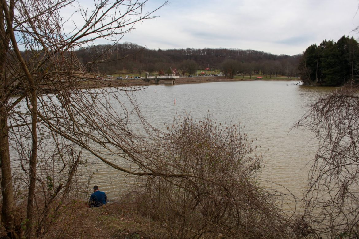 A solo fisherman sits along the bank of North Park Lake on March 22. (Photo by Kimberly Rowen/PublicSource)