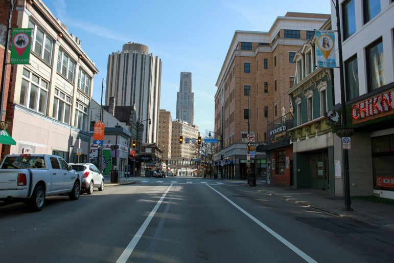 The switch to remote learning for University of Pittsburgh students has caused a large reduction in both vehicle and pedestrian traffic on the usually bustling corridor along Forbes Avenue in Oakland. (Photo by Kimberly Rowen/PublicSource)