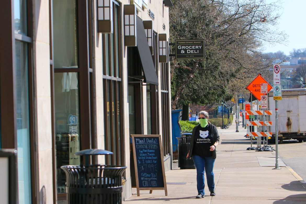 A woman wearing a face mask passes Forbes Street Market on Pitt's Oakland campus on an otherwise pedestrian-free sidewalk on April 6. (Photo by Kimberly Rowen/PublicSource)