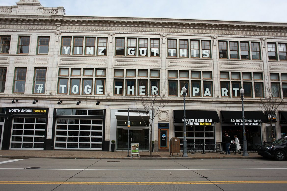 "People carry their takeout food beneath the windows of the Smith Brothers Agency in the North Shore. The windows read ""Yinz Got This, #Together Apart"". (Photo by Kimberly Rowen/PublicSource)"