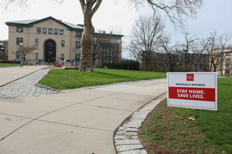 A sign on the campus of Carnegie Mellon University on March 27 reminds people to stay at home and physically distance if they have to go out. The switch to remote learning for the remainder of the semester has left the campus largely vacant. (Photo by Kimberly Rowen/PublicSource)