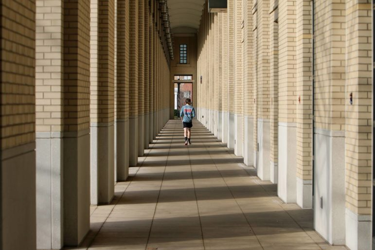 A man walks on the campus of Carnegie Mellon University on March 27. In response to COVID-19, CMU has switched to remote learning for the remainder of the semester and encouraged all students to leave on campus housing if they're able to. (Photo by Kimberly Rowen/PublicSource)