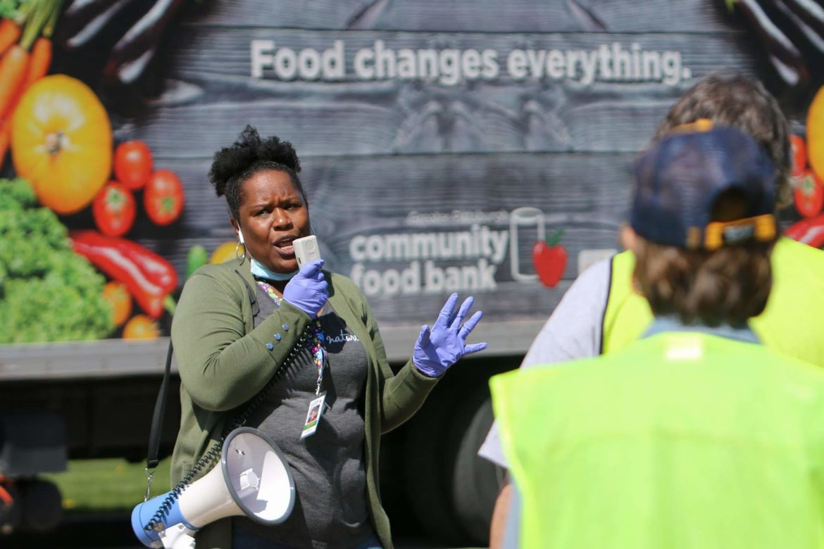 Charlese McKinney gives instructions to a group of volunteers at the Greater Pittsburgh Community Food Bank's emergency drive-up food distribution in Duquesne on April 6. (Photo by Kimberly Rowen/PublicSource)
