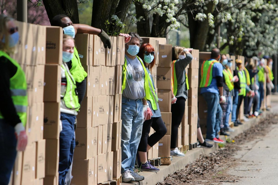 Volunteers in face masks wait for cars to arrive amid the boxes of food they will distribute into the trunks and backseats of cars at the Greater Pittsburgh Community Food Bank's emergency drive-up food distribution in Duquesne on April 6. (Photo by Kimberly Rowen/PublicSource)