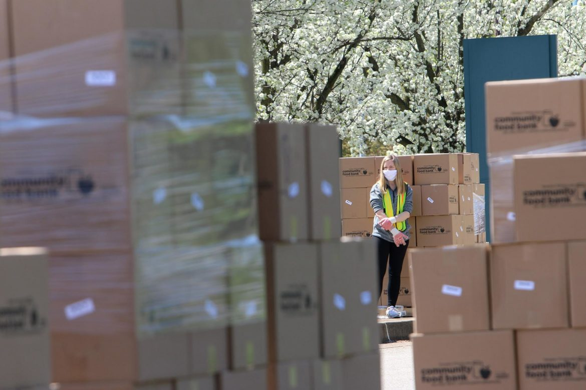 A volunteer waits amid boxes of food during the Greater Pittsburgh Community Food Bank emergency drive-up food distribution in Duquesne on April 6. (Photo by Kimberly Rowen/PublicSource)