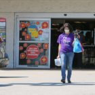 A person wearing a face mask exits Giant Eagle in West Mifflin. (Photo by Kimberly Rowen/PublicSource)