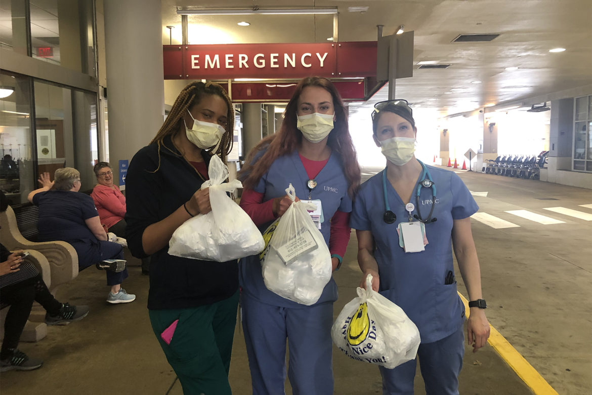 Three healthcare workers collect donated breakfast and coffee for the staff in the Emergency Department at UPMC Presbyterian. Donation money was collected from the community and used to buy food from Friendship Perk & Brew. (Photo from Feeding the Frontline Pittsburgh)