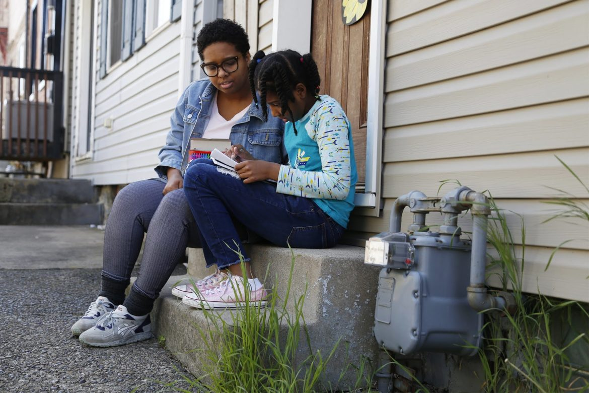 Sitting outside their home in Lawrenceville, Amber Thompson, 34, helps her daughter Audri Young, 9, with school work. (Photo by Ryan Loew/PublicSource)