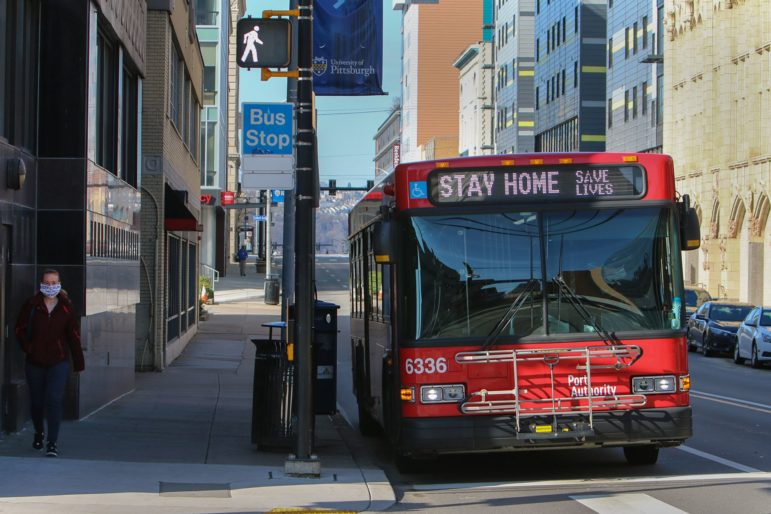 On Forbes Avenue in Oakland, a person wearing a face mask exits a Port Authority bus adorned with the message 'Stay Home, Save Lives'. (Photo by Kimberly Rowen/PublicSource)