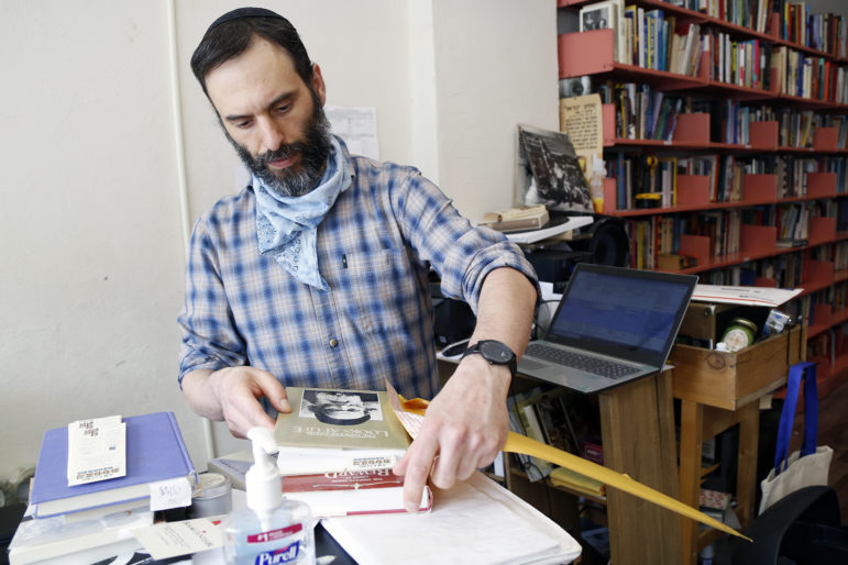 Eric Ackland, owner of Amazing Books and Records, fulfills online orders from his store's Squirrel Hill location. (Photo by Ryan Loew/PublicSource)