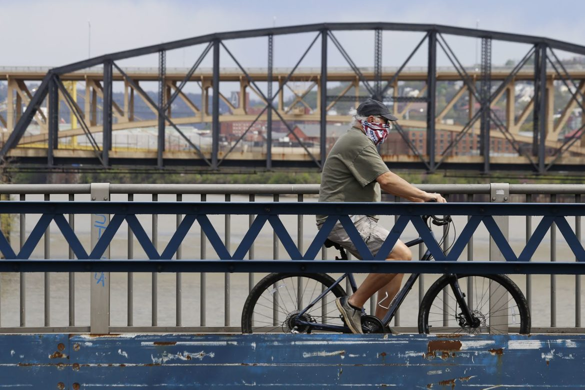 A cyclist wearing a face mask crosses the Smithfield Street Bridge on April 29, 2020. (Photo by Ryan Loew/PublicSource)