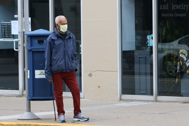 A man waits for the bus along Murray Avenue in Squirrel Hill on March 27. (Photo by Kimberly Rowen/PublicSource)