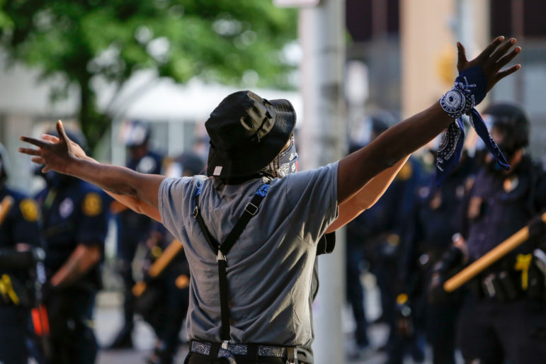 A protester is facing off the police as they announce unlawful assembly before they start firing rubber bullets and tear gas. (Photo by Nick Childers/PublicSource)