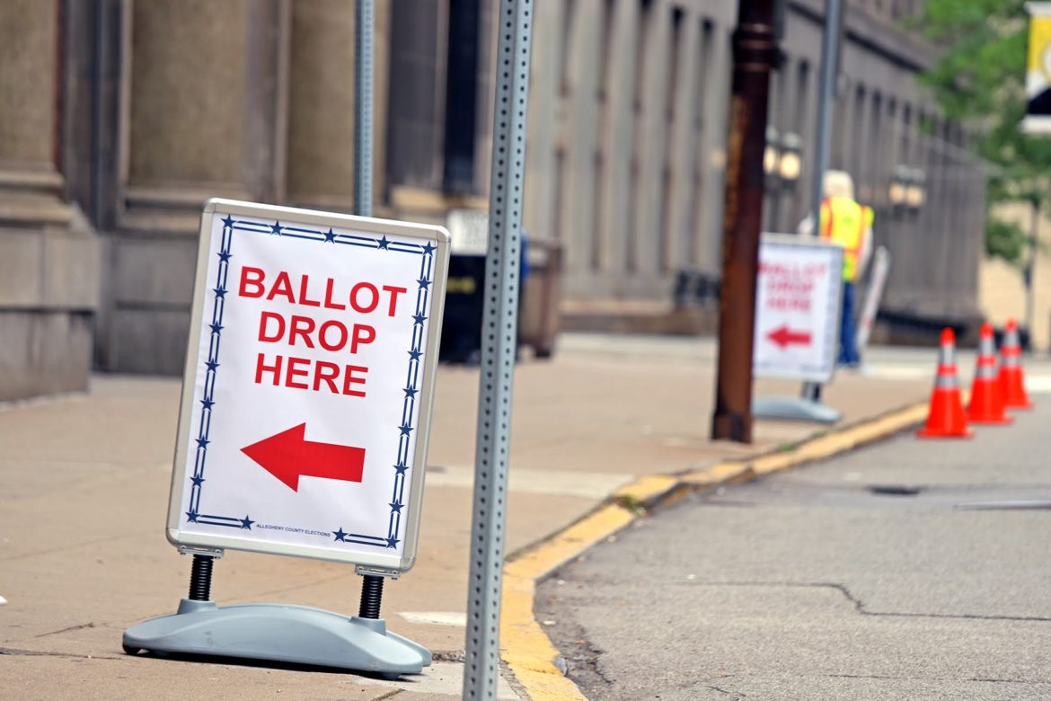 A sign pointing voters to the mail-in ballot drop-off box in the lobby of the Allegheny County Office Building. (Photo by Jay Manning/PublicSource)
