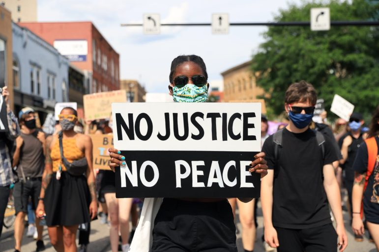 A demonstrator holds a sign at a June 26, 2020 protest against police violence in East Liberty. (Photo by Jay Manning/PublicSource)