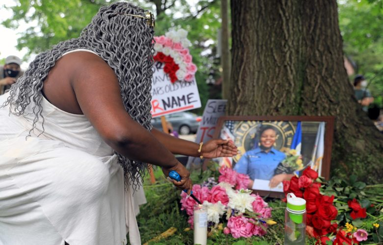 A resident lights a candle for Breonna Taylor during a demonstration in Lyndhurst Green on June 5, 2020. (Photo by Jay Manning/PublicSource)