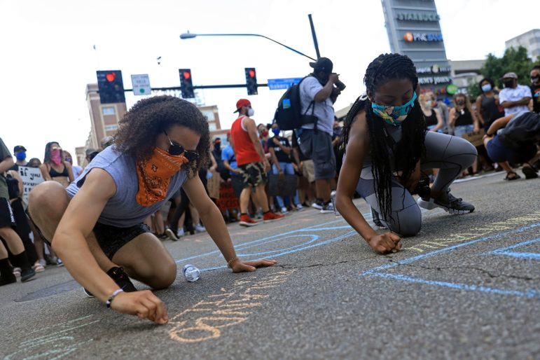 People who attended a June 6 sit-in at Bakery Square in Pittsburgh chalk names of those killed by police violence. (Photo by Jay Manning/PublicSource)