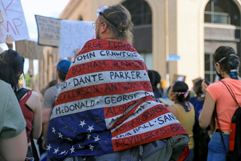 A person at a June 6 protest with the names of people killed by police violence written on an American flag. (Photo by Jay Manning/PublicSource)