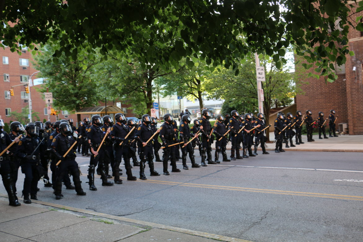 Police in riot gear move into formation near the intersection of Centre and South Negley avenues as protesters advance toward them on Centre Avenue on June 1. (Photo by Alexis Lai/PublicSource)