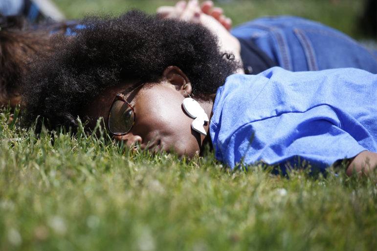 Twelve-year-old Calise Cowans, of Braddock, lies on the ground in silence alongside hundreds of others at Point State Park Sunday for eight minutes and 46 seconds, the amount of time prosecutors say a white Minneapolis police officer had his knee on George Floyd's neck before he died. (Photo by Ryan Loew/PublicSource)