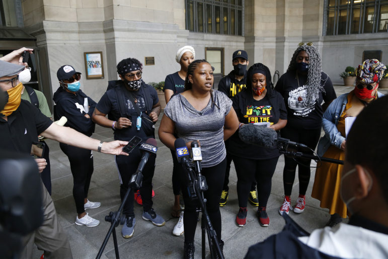 Brandi Fisher, president and CEO of the Alliance for Police Accountability, speaks at a press conference on the portico of the City-County Building.