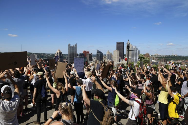 Protesters gather at the Grandview Overlook in Mount Washington on Sunday, listening to speakers before marching to Downtown Pittsburgh. (Photo by Ryan Loew/PublicSource)